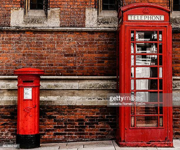 Mailbox And Telephone Booth Against Brick Wall