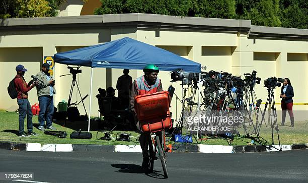 A mailman rides in front of some of the media camping outside the Johannesburg home of South Africa's antiapartheid icon Nelson Mandela on September...