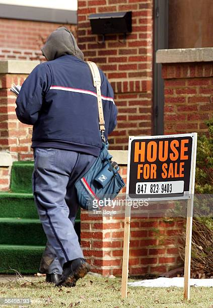 A mailman walks past a 'House For Sale' sign in front of a house December 29 2005 in Park Ridge Illinois Sales of existing homes in November fell...