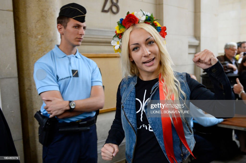 Main activist of Ukrainian feminist protest group Femen Ukraine's Inna Shevchenko walk toward the courtroom after checking through security prior to her hearing, along with eight other activists, on charges of damaging Notre Dame cathedral during a demonstration earlier this year, on September 13, 2013 at Paris courthouse. On February 12, Femen activists, who had previously alerted news agencies, hid in the lines of tourists streaming into the historic cathedral before perching on the base of three new bells temporarily placed in the nave.