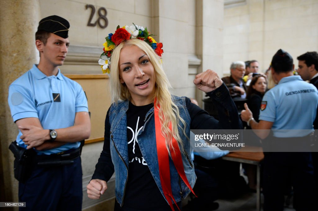 Main activist of Ukrainian feminist protest group Femen Ukraine's Inna Shevchenko walks toward the courtroom after checking through security prior to her hearing, along with eight other activists, on charges of damaging Notre Dame cathedral during a demonstration earlier this year, on September 13, 2013 at Paris courthouse. On February 12, Femen activists, who had previously alerted news agencies, hid in the lines of tourists streaming into the historic cathedral before perching on the base of three new bells temporarily placed in the nave. AFP PHOTO LIONEL BONAVENTURE
