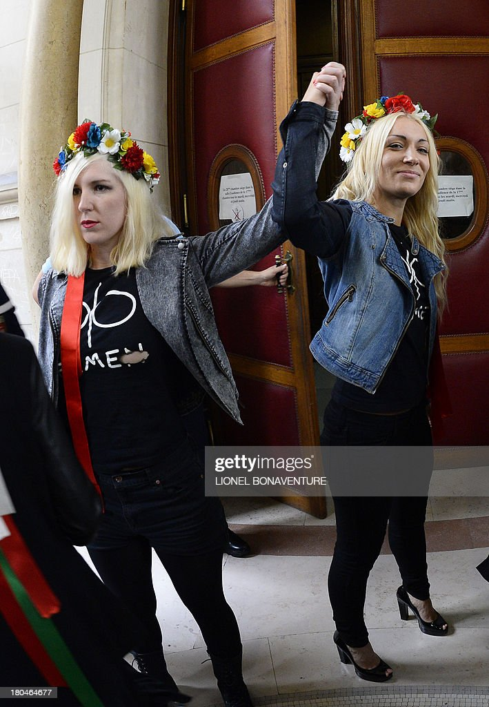 Main activist of Ukrainian feminist protest group Femen Ukraine's Inna Shevchenko (R) and an unidentified Femen activist raise their fists as they walks toward the courtroom prior to their hearing, along with seven other activists, on charges of damaging Notre Dame cathedral during a demonstration earlier this year, on September 13, 2013 at Paris courthouse. On February 12, Femen activists, who had previously alerted news agencies, hid in the lines of tourists streaming into the historic cathedral before perching on the base of three new bells temporarily placed in the nave.