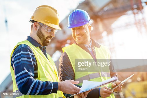 Main engineer showing report to contractor at construction site