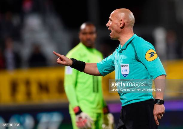 Main referee Amaury Delerue gestures during the French L1 football match between Nancy and Lille at Marcel Picot Stadium in Tomblaine on March 11...
