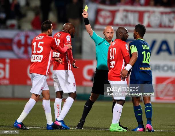 Main referee Amaury Delerue gives a yellow card during the French L1 football match between Nancy and Lille at Marcel Picot Stadium in Tomblaine on...