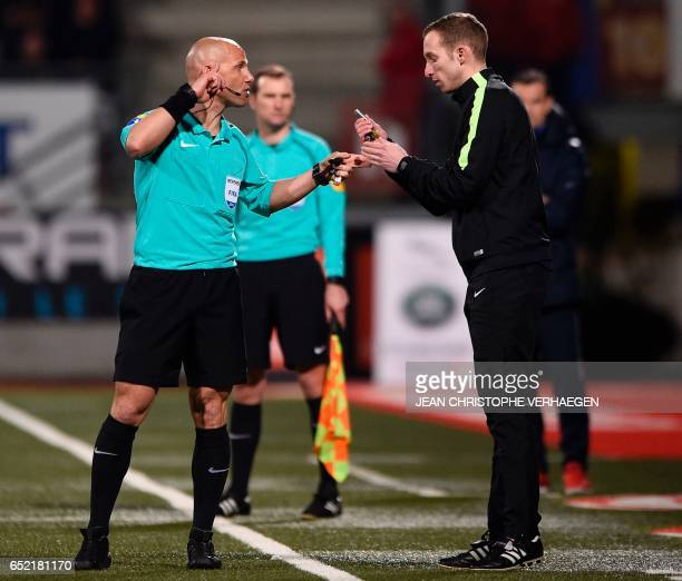 Main referee Amaury Delerue gives lighters thrown by supporters to assistant referee Remi Landry during the French L1 football match between Nancy...