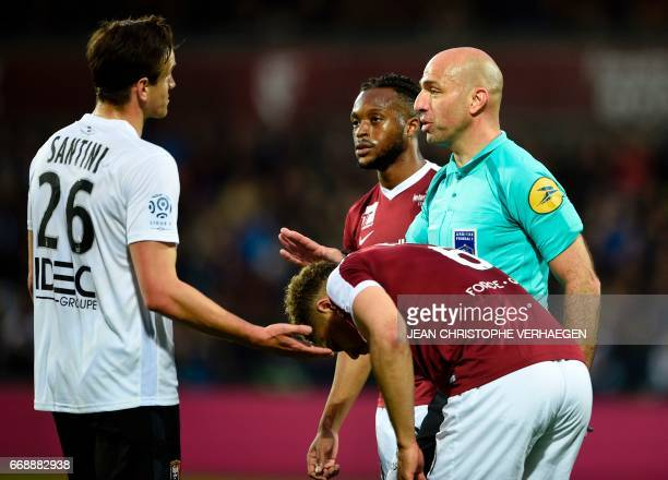 Main referee Bartolomeu Varela speaks with Caen's Croatian forward Ivan Santini during the French L1 football match between Metz and Caen on April 15...