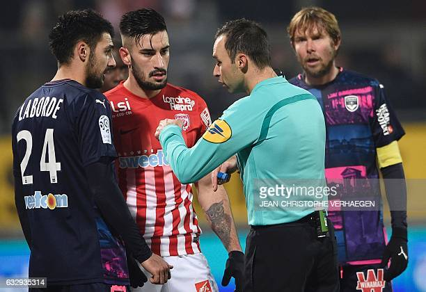 Main referee Jerome Brisard speaks with Nancy's SpanishUruguayan defender Erick Cabaco and Bordeaux' French forward Gaetan Laborde during the French...