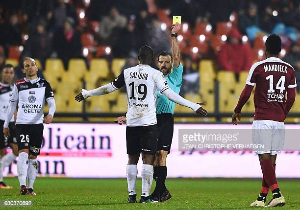 Main referee Sebastien Desiage gives a yallow card to Guingamp's French midfielder Yannis Salibur during the French L1 football match between Metz...