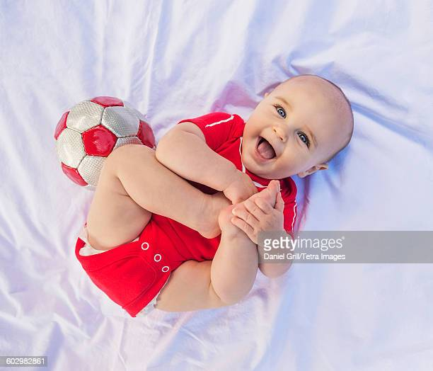 USA, Maine, Camden, Portrait of baby boy (6-11 months) lying down with soccer ball