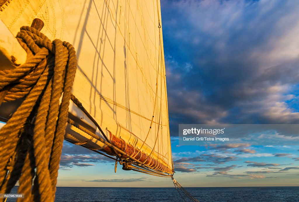 USA, Maine, Camden, Sail and ropes against sunset sky