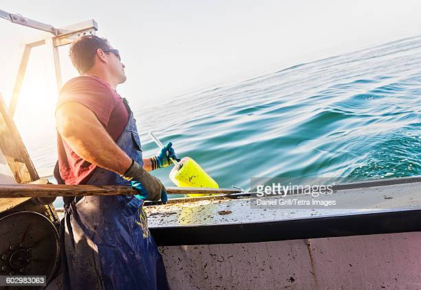 USA, Maine, St. George, Fisherman throwing lobster buoy