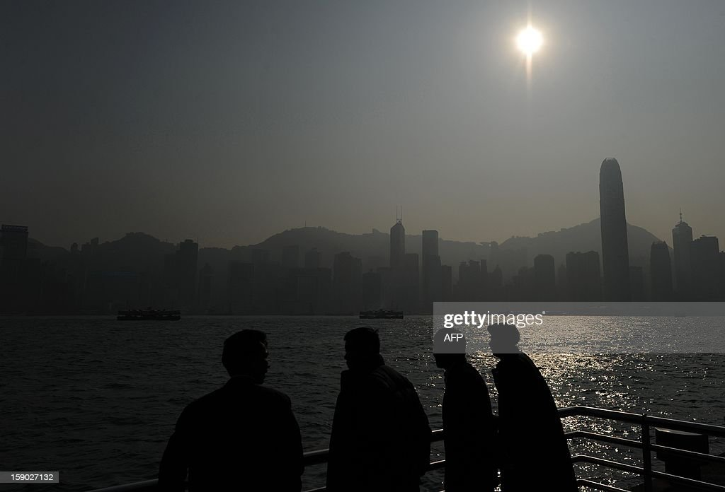 Mainland Chinese men look out at the city skyline in Hong Kong on January 6, 2013. The International Monetary Fund on December 12, 2012 warned Hong Kong could see an abrupt fall in property prices after years of dramatic increases in one of the world's most expensive housing markets. AFP PHOTO / Dale de la Rey