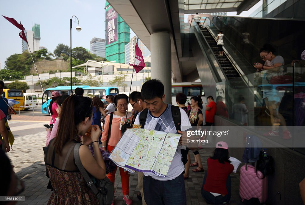 A mainland Chinese tourist looks at a map on Avenue of Stars in Hong Kong China on Thursday Oct 2 2014 Chinese tourists are descending on Hong Kong...