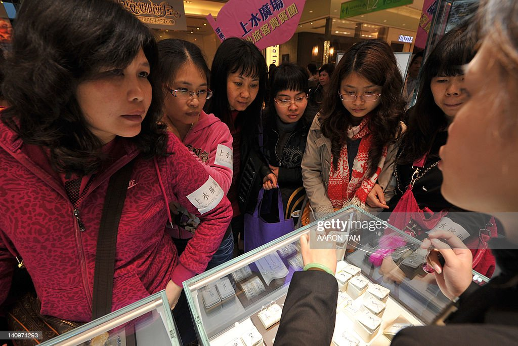 Mainland Chinese tourists look at a display at a jewelry store in a Hong Kong shopping mall on March 8 2012 AFP PHOTO / AARON TAM
