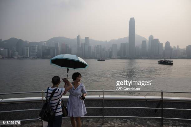 Mainland Chinese tourists stand on a viewing platform in front of the city skyline on a polluted day in Hong Kong on September 17 2017 / AFP PHOTO /...