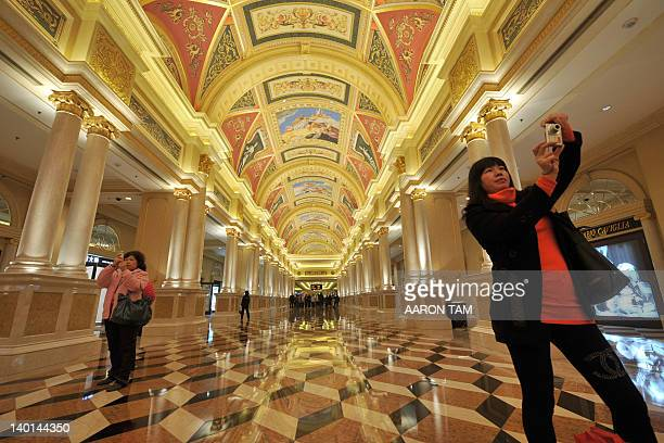 Mainland Chinese tourists take pictures inside The Venetian hotel and casino resort in Macau on February 29 2012 The economy of Macau a former...