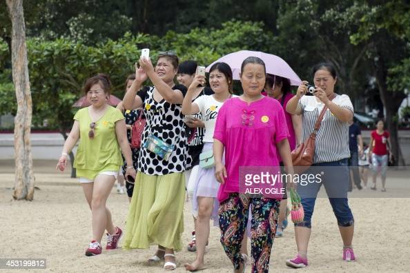 Mainland Chinese tourists walk from their tour bus to a beach in Hong Kong on August 5 2014 A Hong Kong lifeguards union announced they would to go...