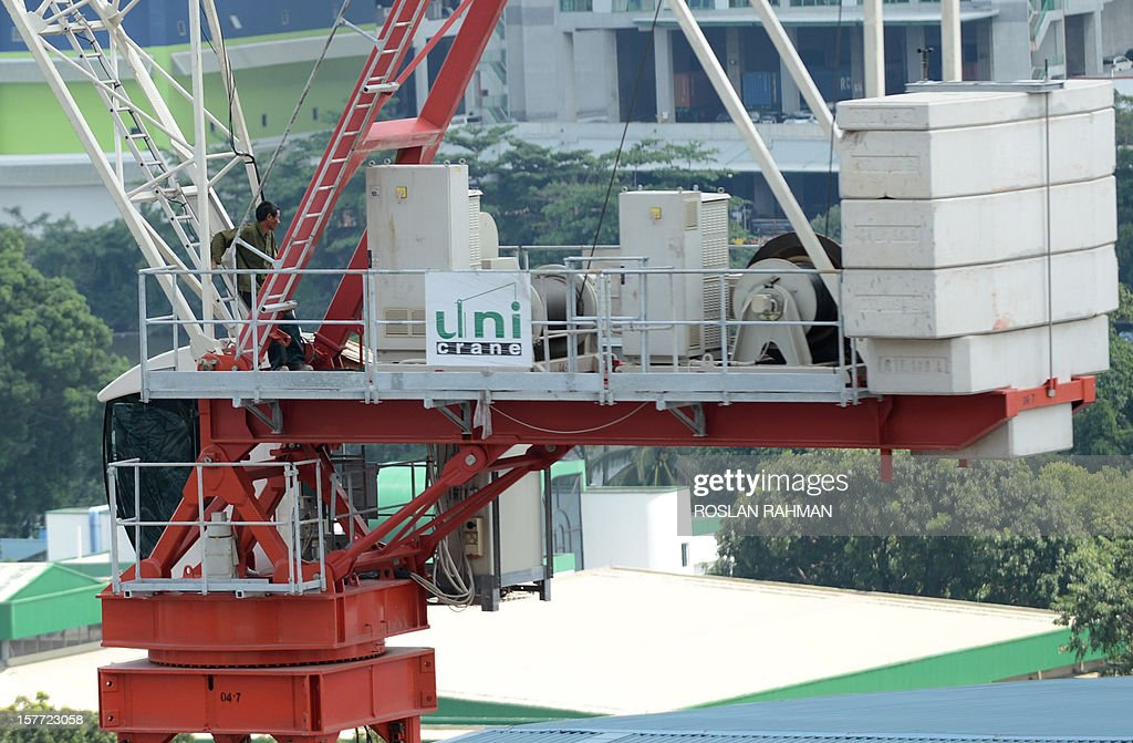 A mainland Chinese worker stands on top of a crane after refusing to come down during a protest at a construction site in Singapore on December 6, 2012. Two crane operators staged a high-rise protest at a construction site in Singapore on December 6, its second industrial incident involving mainland Chinese workers in less than two weeks.