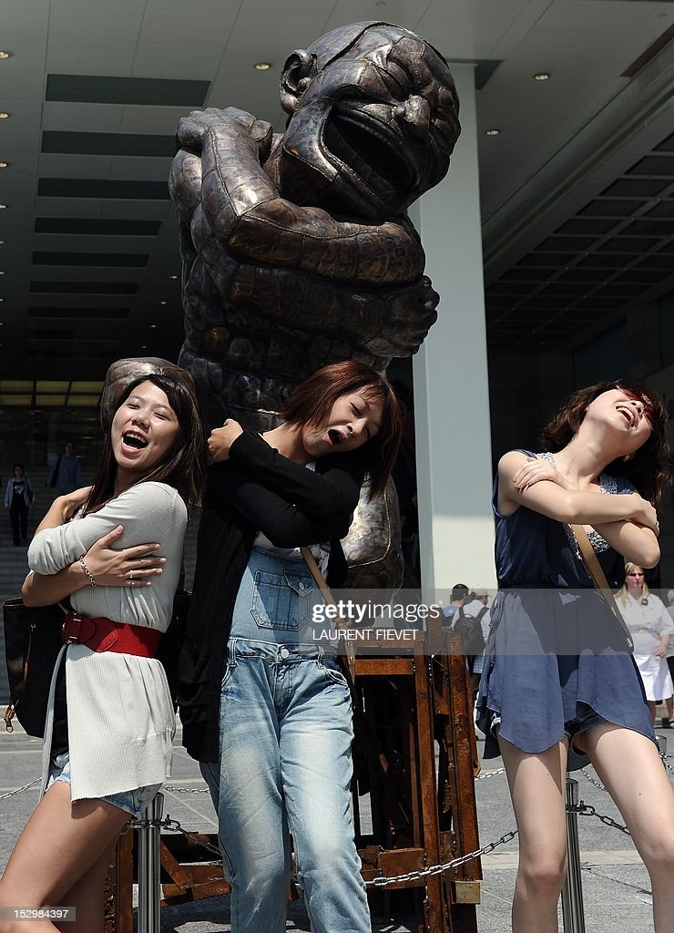 Mainland tourists pose for a photograph next to a sculpture by Chinese born artist Yue Minjun during an outdoor exhibition in Hong Kong on September 29, 2012. Yue Minjun is a contemporary Chinese artist based in Beijing and is best known for oil paintings depicting himself in various settings like 'frozen in laughter.'
