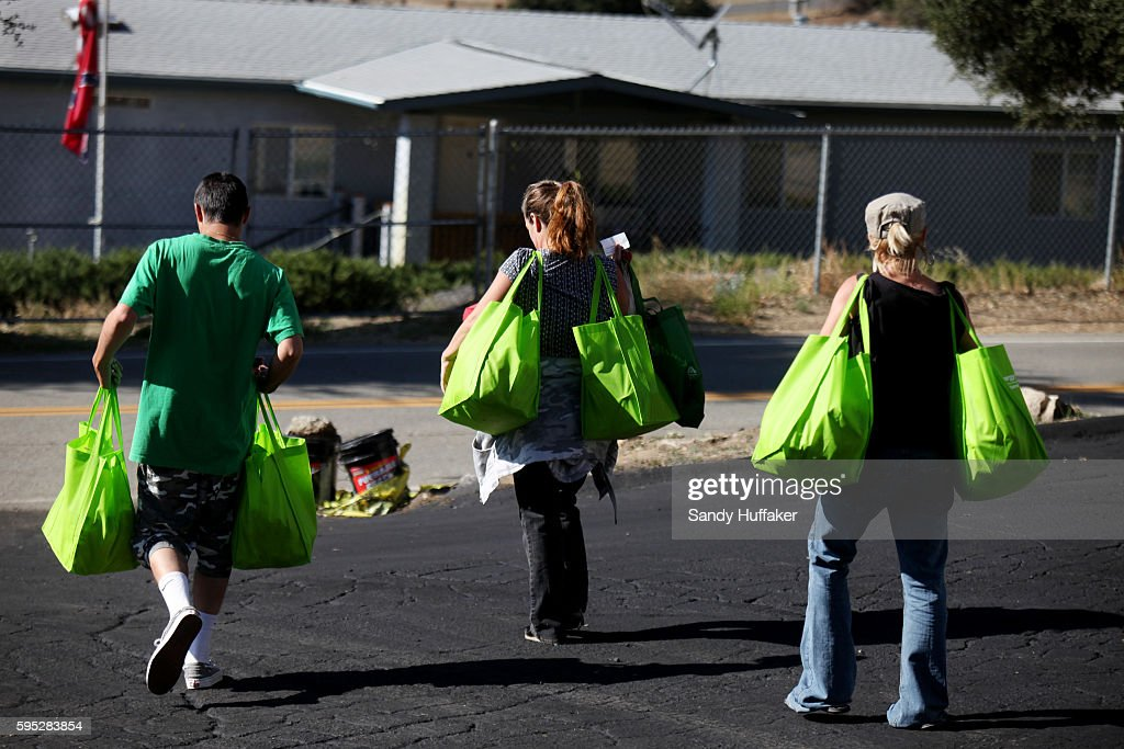 Mainly poor and elderly residents take donated food items to their vehicles after receiving them from a Feeding America truck on Thursday November 3...