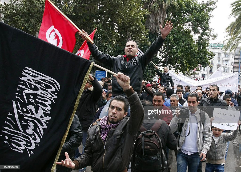 Mainly Tunisian Ennahda Islamist party supporters shout slogans as they march along Habib Bourguiba Avenue in the capital Tunis, on December 8, 2012, demanding that cronies of ousted dictator Zine El Abidine Ben Ali be put in the dock on corruption charges. The rally was organised by the League for the Protection of the Revolution, a group close to the ruling Islamist Ennahda party, which claims its mission is to protect the goals of the 2011 revolution that toppled Ben Ali.