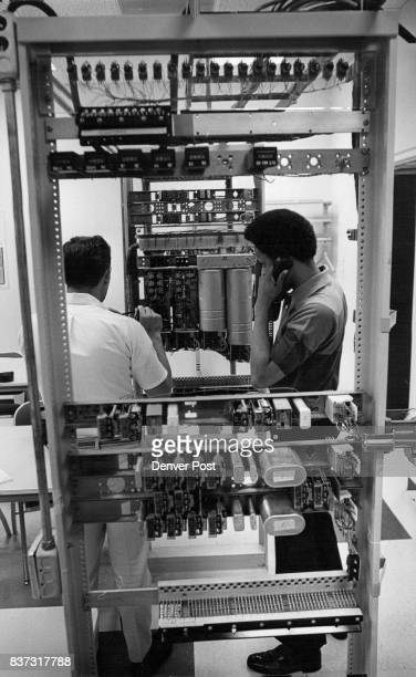 K Mains left of Tucson Ariz and JA Allen of Denver check operation of a selector switch utilized in switching calls in the big fastacting system...