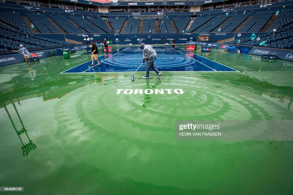 TOPSHOT Maintenance crews work to dry the court after a rain delay at Rogers Cup tennis in Toronto Canada July 31 2016 / AFP / KEVIN VAN PAASSEN