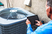 Maintenance engineer using digital tablet to inspect air conditioning unit