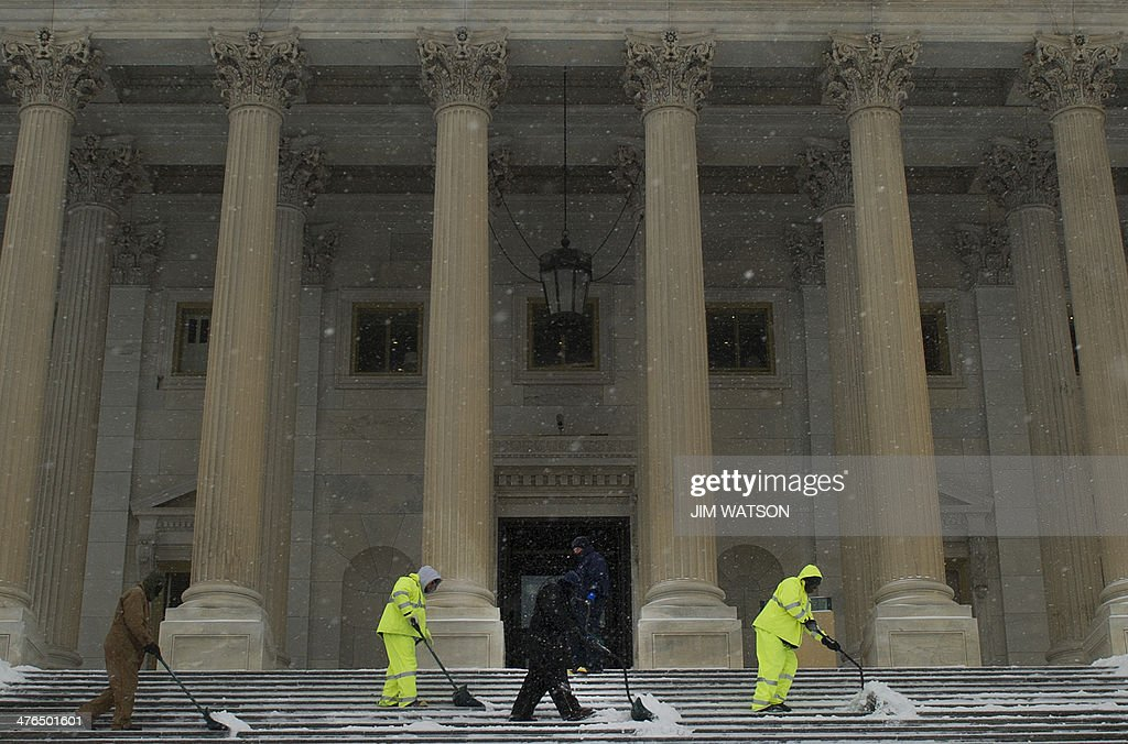 Maintenance men shovel snow from the House steps at the US Capitol in Washington, DC, March 3, 2014 after an early morning snow storm. Snow began falling in the nation's capital early Monday, and officials warned people to stay off treacherous, icy roads a scene that has become familiar to residents in the Midwest, East and even Deep South this year. Schools were canceled, bus service was halted in places and federal government workers in the DC area were told to stay home Monday. AFP PHOTO / Jim WATSON