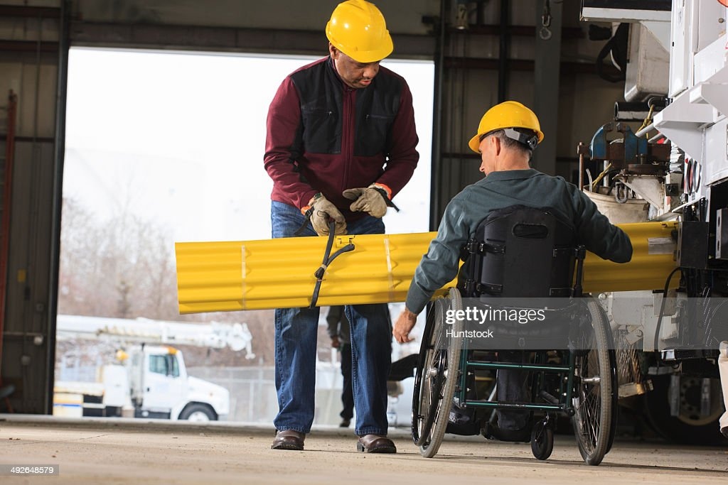 Maintenance supervisors one with spinal cord injury loading shielding onto utility truck