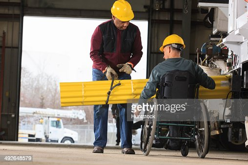 Maintenance supervisors one with spinal cord injury loading shielding onto utility truck : Stock Photo