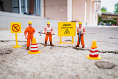 Under construction warning , Maintenance team to repair street cracked , Miniature figure with warning sign on concrete street cracked
