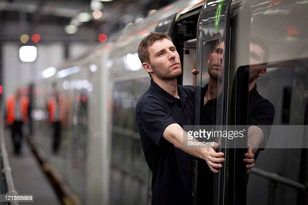 A maintenance technician examines passenger doors on a Siemens AG 350 class train at the company's Kings Heath train maintenance depot in Northampton...