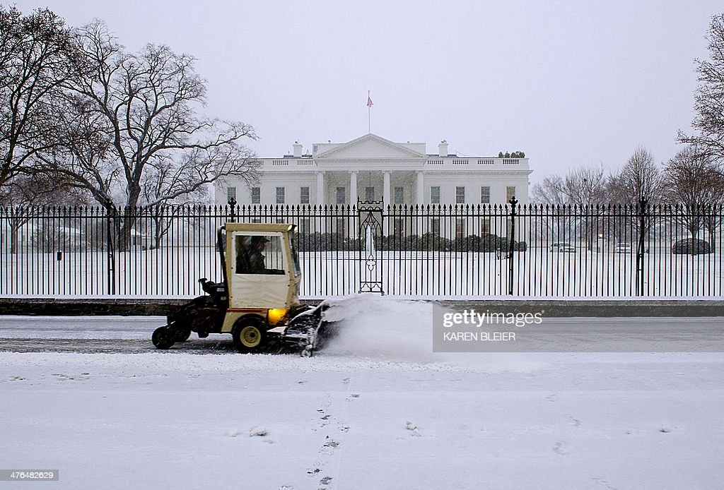 A maintenance worker brushes snow from the walkway in front of the White House during a snow strom March 3, 2014 in Washington, DC. Snow began falling in the nation's capital early Monday, and officials warned people to stay off treacherous, icy roads a scene that has become familiar to residents in the Midwest, East and even Deep South this year. Schools were canceled, bus service was halted in places and federal government workers in the DC area were told to stay home Monday. AFP PHOTO / Karen BLEIER