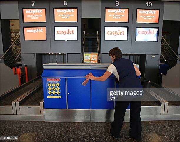 A maintenance worker cleans a CheckIn counter in an empty departures hall at Belfast International airport in Northern Ireland on April 16 2010...