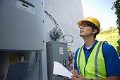 Maintenance worker reads meter of solar generation unit in Los Angeles, California