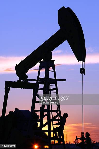Maintenance workers climb a China National Petroleum Corp's 'nodding donkey' oil pump at sunset on July 13 2006 in Daqing Heilongjiang province China...
