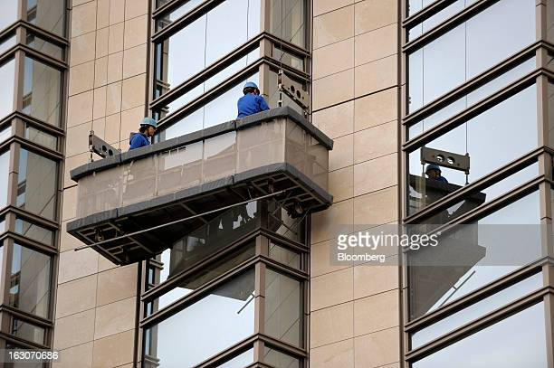 Maintenance workers stand on a suspended platform as they clean the windows of Hyatt Hotels Corp's Grand Hyatt Tokyo hotel adjacent to Mori Building...