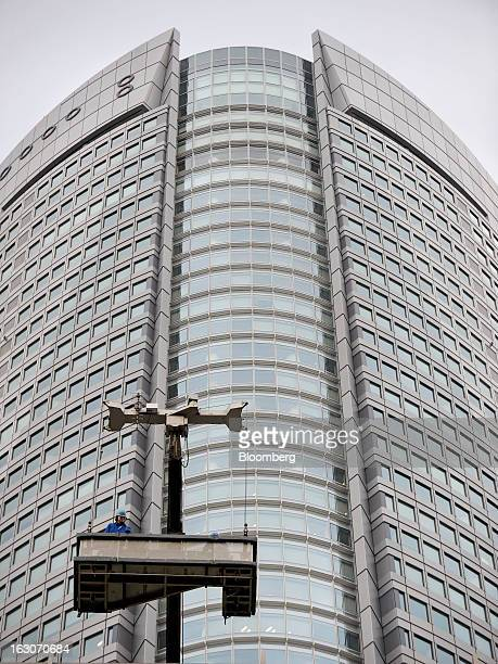 Maintenance workers stand on a suspended platform in front of Mori Building Co's Roppongi Hills Mori Tower as they prepare to clean the windows of...