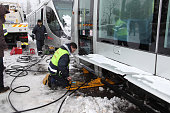 Maintenance workers use a hydraulic jack powered by a portable generator as they attempt to reseat light rail cars on their tracks after a derailment...
