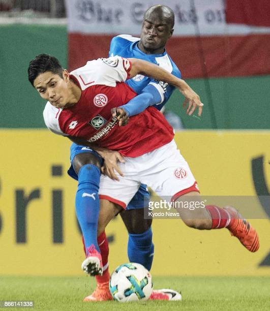 Mainz forward Yoshinori Muto shields the ball away from Holstein Kiel's Amara Conde on Oct 24 in the second round of the German DFB Cup ==Kyodo