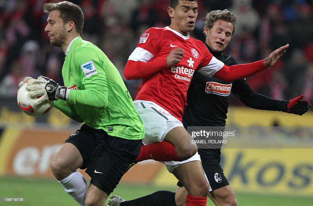 Mainz' striker Shawn Parker (C) and Freiburg's goalkeeper Oliver Baumann (L) vie for the ball during the German first division Bundesliga football match FSV Mainz 05 vs SC Freiburg in Mainz, southwestern Germany, on January 19, 2012.