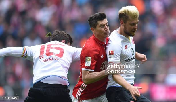 Mainz's defender Stefan Bell Bayern Munich's Polish striker Robert Lewandowski and Mainz's defender Alexander Hack vie for the ball during the German...