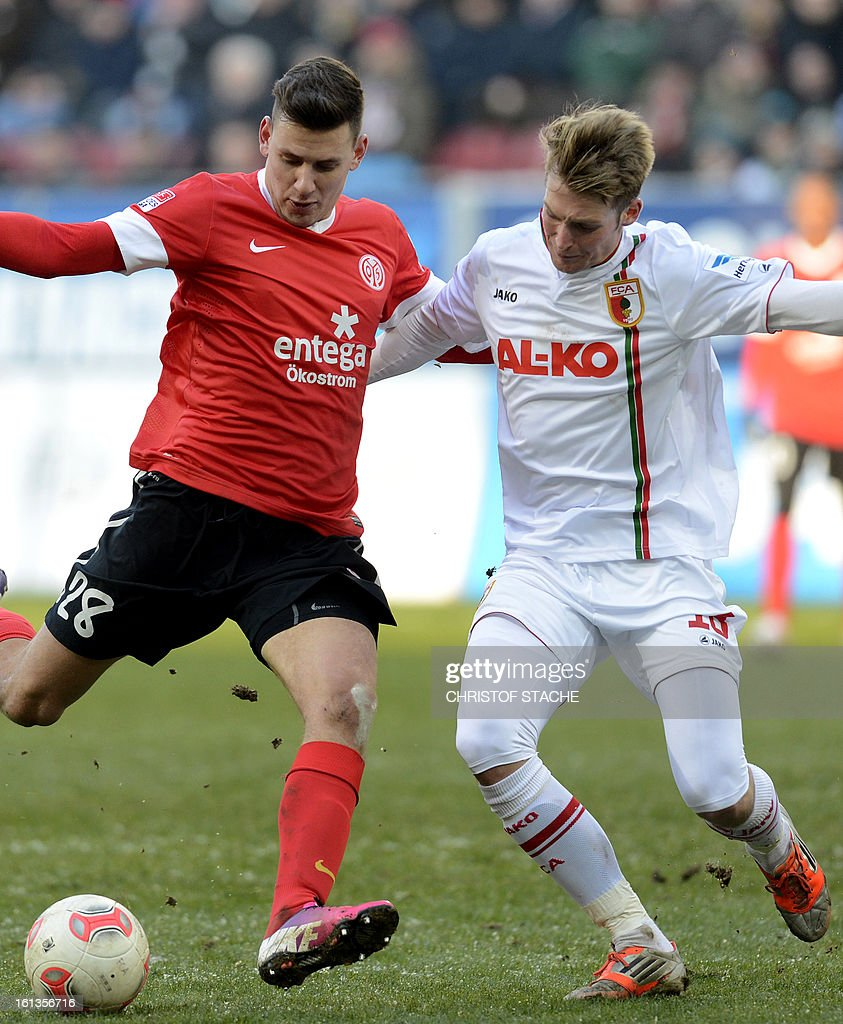 Mainz's Hungarian striker Adam Szalai (L) and Augsburg's midfielder Jan-Ingwer Callsen-Bracker (R) challenge for the ball during the German first division Bundesliga football match between FC Augsburg and FSV Mainz 05 in Augsburg, southern Germany, on February 10, 2013.