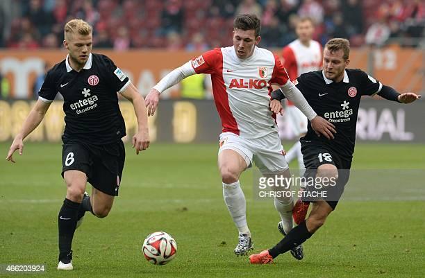 Mainz's midfielder Johannes Geis Augsburg's Danish midfielder Pierre Emile Hojbjerg and Mainz's defender Daniel Bengtsson vie for the ball during the...