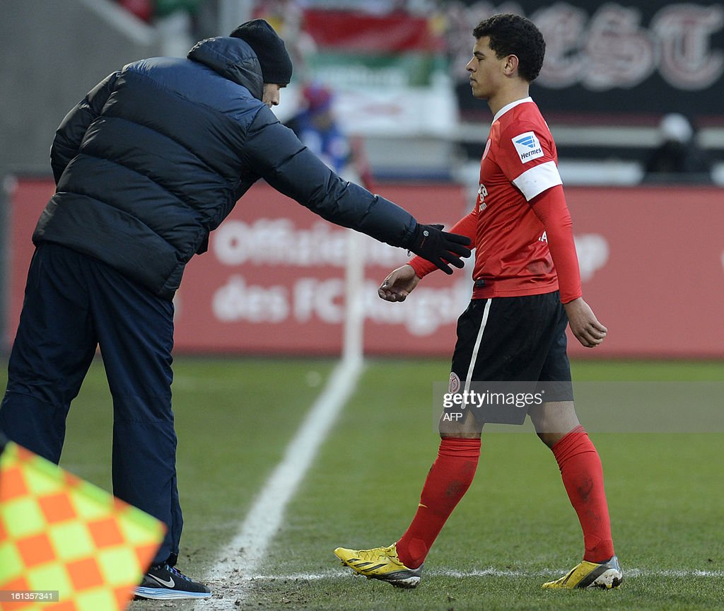 Mainz's striker Shawn Parker (R) leaves the field after he got the red card beside his coach Mainz's headcoach Thomas Tuchel (L) during the German first division Bundesliga football match between FC Augsburg and FSV Mainz 05 in Augsburg, southern Germany, on February 10, 2013.