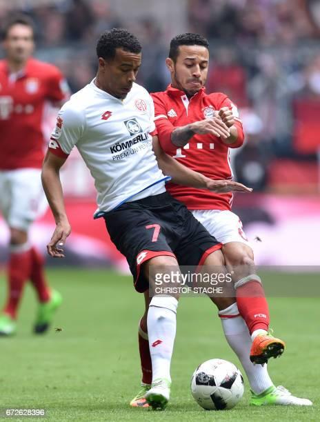 Mainz's Swedish midfielder Robin Quaison and Bayern Munich's Spanish midfielder Thiago Alcantara vie for the ball during the German first division...
