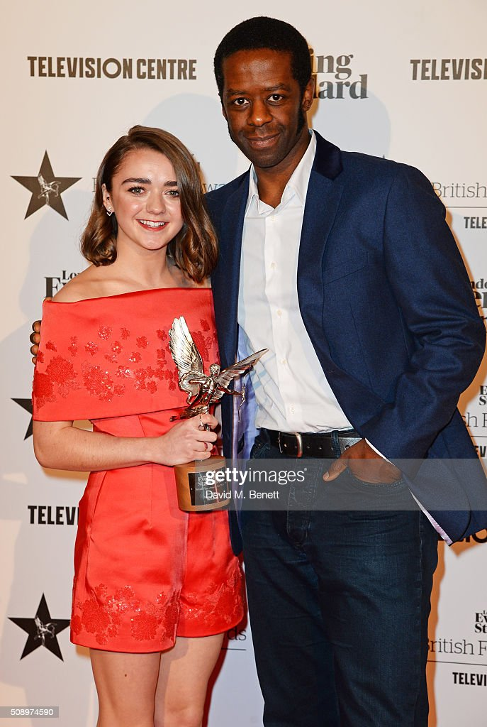 Maisie Williams winner of the Rising Star award for 'The Falling' and presenter Adrian Lester pose in front of the Winners Boards at the London...