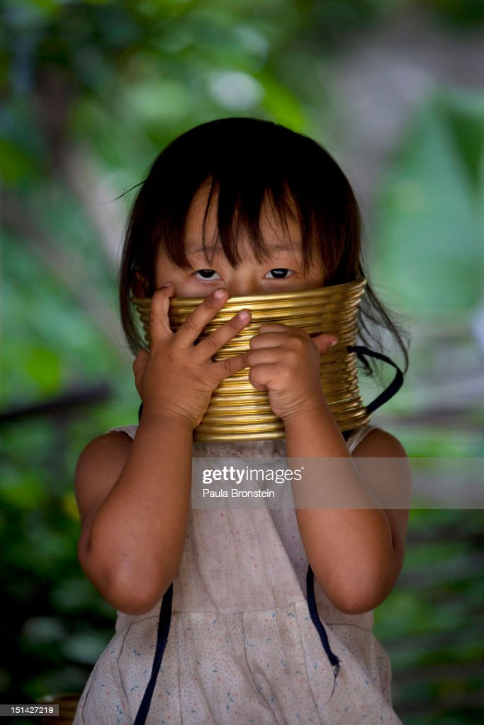 Maiyu, 3, plays with the gold neck rings that are for tourists to try on September 4, 2012 in Maerim, Thailand. Baan Tong Luang is a fabricated village containing 6 separate Thai Hill Tribes where visitors are expected to pay $16 or 500 Thai bhat for the entrance fee. The ethnic tribes include the Lahu, Hmong, White Karen, Long necked Karen, Yao, Akha. The village opened since 2005 attempts to preserve the old traditions of the ethnic Hill Tribe, also providing an income for them. Life for many of Thailand's Hill Tribe population can be difficult since it can be hard for them to make a living. Their language, costume and culture are different along with the frequent legal problems over Thai citizenship. Hill tribe is a term used in Thailand for all of the various tribal peoples who migrated from Tibet, or elsewhere in China over the past few centuries.